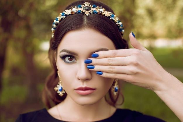 Close-upportret van jonge vrouw met heldere blauwe make-up en blauwe manicure, blauwe decoratie. make-up en manicure in dezelfde stijl. schoonheid, mode, make-up, manicure.