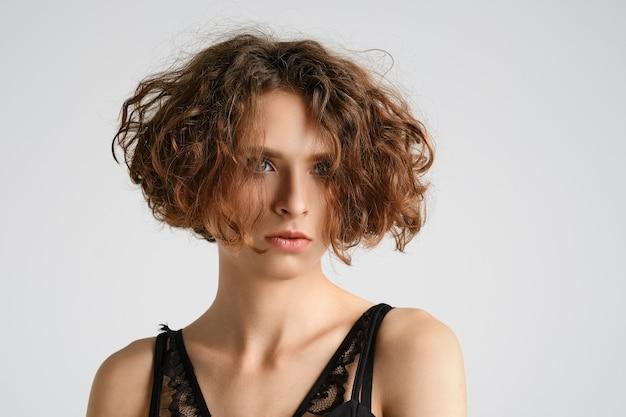 Close-upportret van jonge vrouw met kort krullend haar