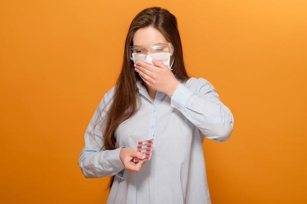 Close-upportret van jonge vrouw op geeloranje in beschermend medisch masker met coronavirus symptoom, pillen in handen, hoest en koorts, coronavirus pandemie