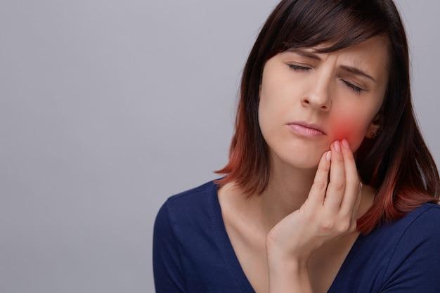 Close-upportret van jonge vrouw op grijze achtergrond die aan tandpijn lijden.