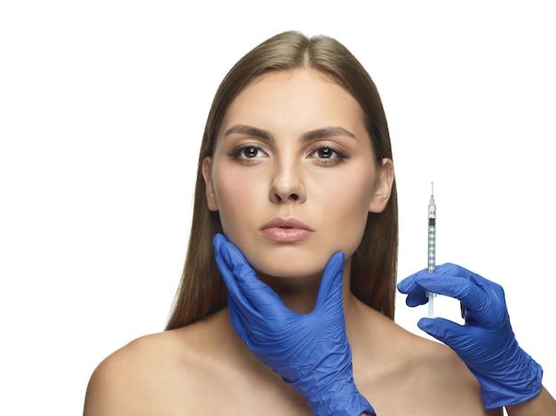 Close-upportret van jonge vrouw op witte muur. operatieprocedure vullen. gezichtscontouren. concept van gezondheid en schoonheid van vrouwen, cosmetologie, zelfzorg, lichaams- en huidverzorging. anti-veroudering.