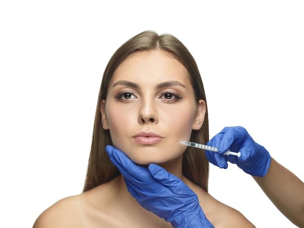 Close-upportret van jonge vrouw op witte studiomuur. operatieprocedure vullen. lipvergroting.