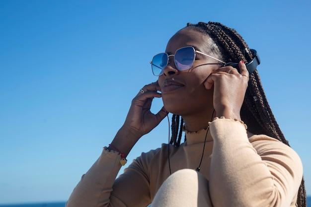 Close-upportret van jonge zwarte afrovrouw die met hoofdtelefoons en blauwe hemelachtergrond glimlacht, mooi afromeisje die positiviteit en vrede overbrengen.