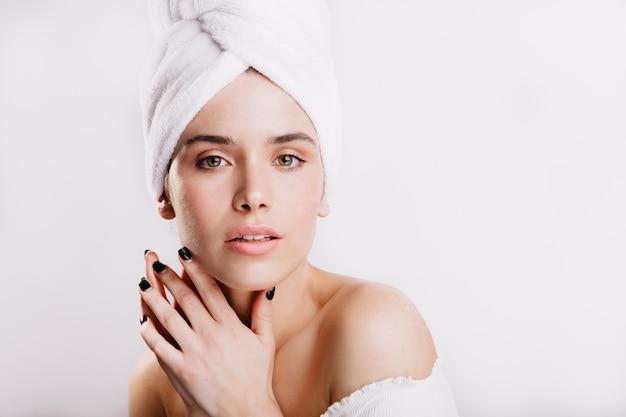 Close-upportret van kalme vrouw in handdoek na douche. dame met groene ogen en geen make-up