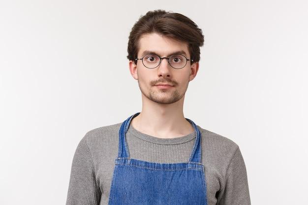 Close-upportret van kaukasische jonge mannelijke student die deeltijds in koffiewinkel werken, zijn carrière in de restaurantindustrie beginnen, schort dragend luisterend aan klantenorde,