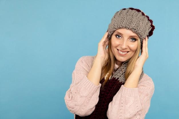 Close-upportret van knappe glimlachende vrouw in de sjaal van de de winterhoed die over de blauwe achtergrond wordt geïsoleerd.