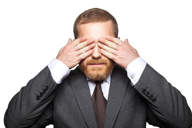 Close-upportret van knappe zakenman met gezichtsbaard in zwart kostuum die zich bevinden en zijn ogen sluiten en niet willen kijken. indoor studio opname geïsoleerd op een witte achtergrond.