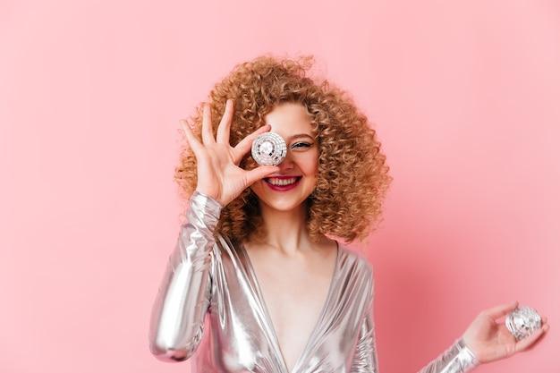 Close-upportret van krullend blondemeisje met charmante glimlach die oog behandelen met minidisco bal op roze ruimte.