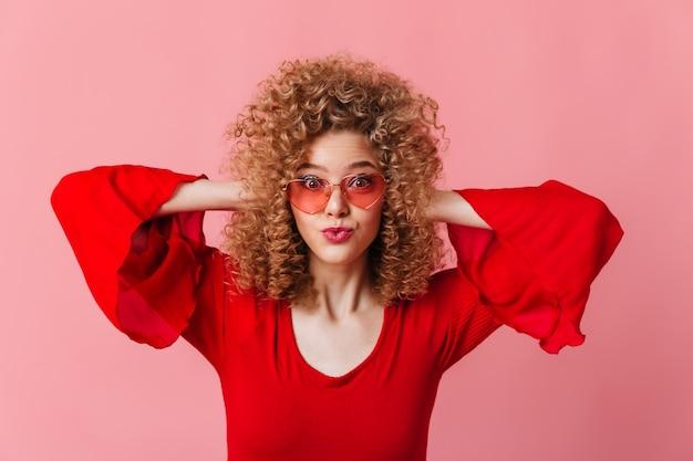Close-upportret van krullende blonde in roze zonnebril en rode bovenkant die op roze ruimte wordt verrast.