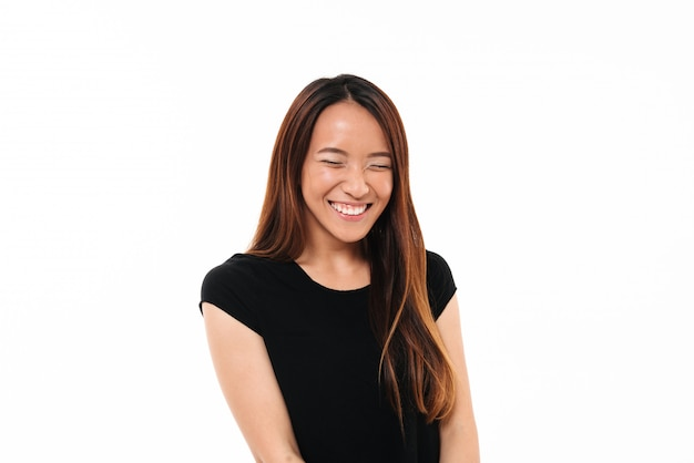 Close-upportret van lachende aantrekkelijke aziatische vrouw met gesloten ogen die op wit wordt geïsoleerd