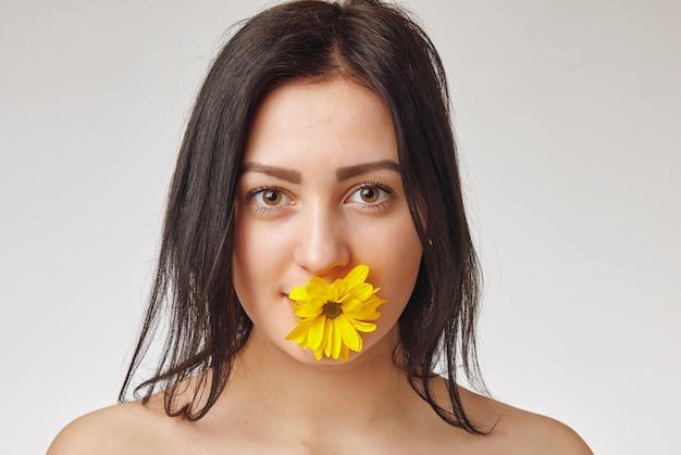 Close-upportret van leuk jong meisje met gele bloem in lippen Premium Foto