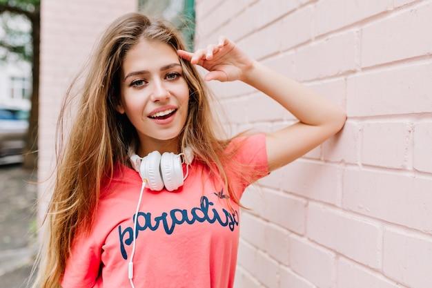 Close-upportret van leuk meisje met lang haar en mooie glimlach die zich naast muur bevinden