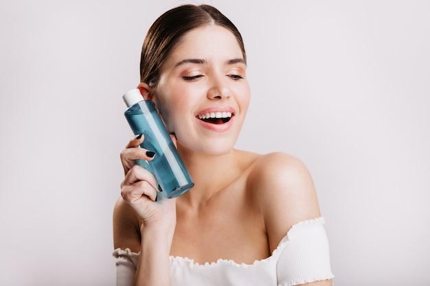 Close-upportret van leuk meisje zonder make-up die blauwe fles met genezend tonicum voor gezichtshuid houden.