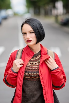 Close-upportret van leuk peinzend meisje in rood jasje en rugzak op de straat