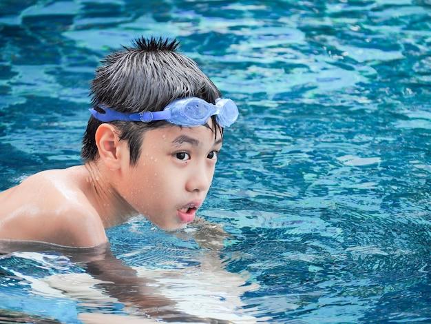 Close-upportret van leuke jongen in het zwembad