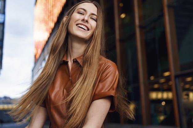 Close-upportret van levendig gelukkig jong meisje glimlachen, op zoek camera vrolijk buitenshuis.
