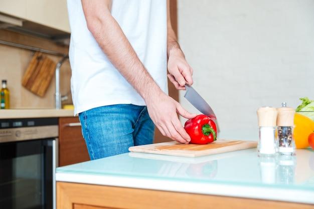 Close-upportret van mannelijke handen die groenten snijden bij de keuken