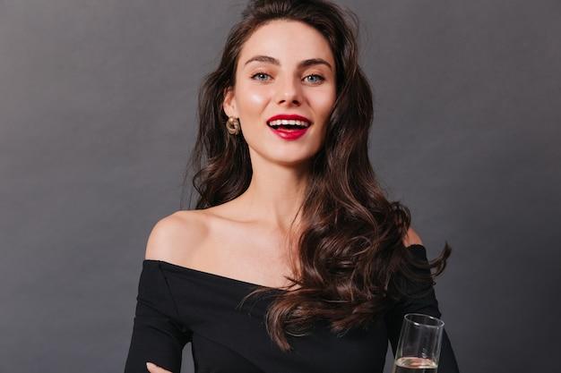 Close-upportret van meisje met heldere blauwe ogen en rode lippenstift. dame in zwarte bovenkant glimlacht en houdt glas witte wijn op donkere achtergrond.