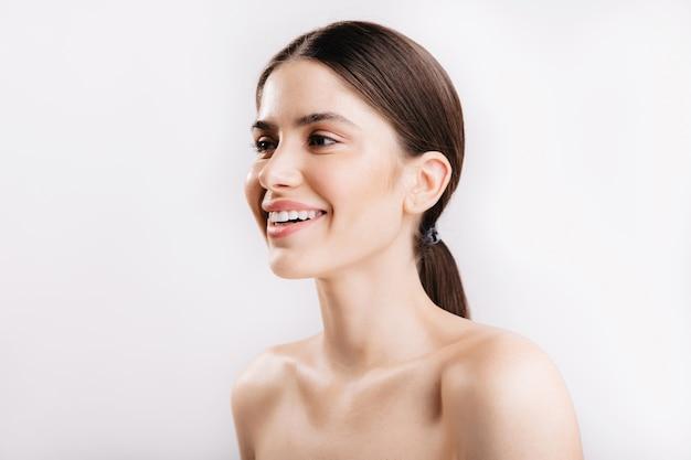Close-upportret van meisje met perfect heldere huid en glanzend gezond haar, poseren met sneeuwwitte glimlach op geïsoleerde muur.