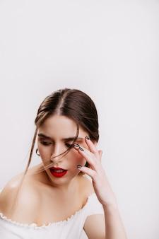Close-upportret van meisje met perfecte huidskleur en rode lippen die haar op witte muur spelen.