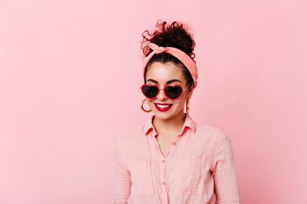 Close-upportret van meisje met rode lippen en broodje in zonnebril. vrouw in roze hoofdband en katoenen overhemd glimlacht op geïsoleerde ruimte.