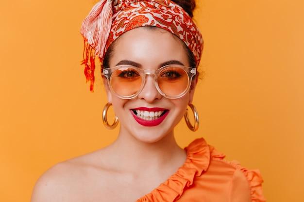 Close-upportret van modieuze dame met rode lippenstift, sneeuwwitte glimlach op oranje ruimte. vrouw in hoofddoek en enorme oorbellen camera kijken.