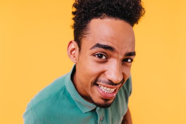 Close-upportret van modieuze vrolijke jongen met bruine ogen. afrikaans mannelijk model in groene outfit die oprechte emoties uitdrukt.