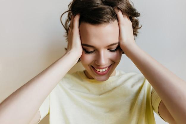 Close-upportret van moe maar glimlachend meisje. foto van mooie jonge vrouw met kort donker haar lachend met gesloten ogen op lichte muur.