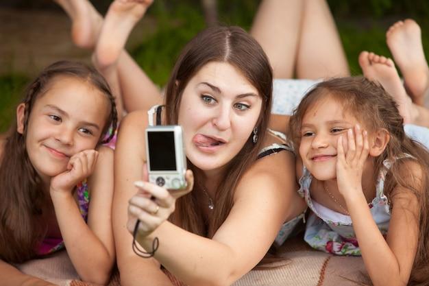 Close-upportret van moeder en dochters die gezichten maken op zelfschot