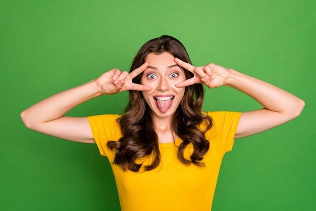 Close-upportret van mooi gek vrolijk meisje dat dubbel v-teken toont die prettijd voor de gek houden geïsoleerd