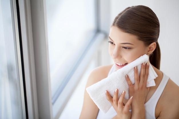 Close-upportret van mooi gelukkig glimlachend meisje die schone witte handdoek houden dichtbij gezichtshuid