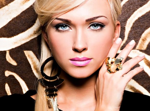 Close-upportret van mooi gezicht van sexy vrouw met maniermake-up en gouden ring aan vinger