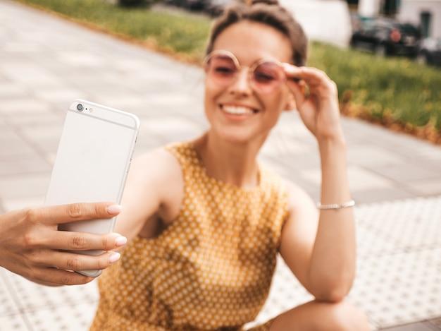 Close-upportret van mooi glimlachend donkerbruin meisje in de zomer hipster gele kleding. model nemen selfie op smartphone. vrouw maken van foto's in warme zonnige dag in de straat in zonnebril