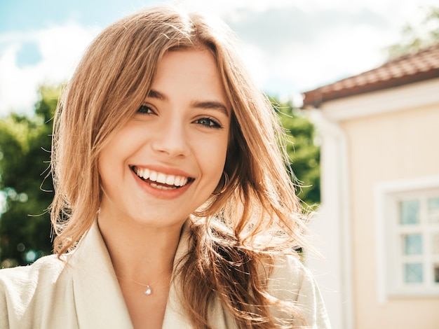 Close-upportret van mooi glimlachend donkerbruin model. trendy vrouw die op straat poseert