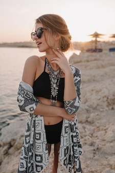 Close-upportret van mooi jong meisje op strand, genietend van zonsondergang, sensueel op zoek naar kant. trendy zwart zwempak, bikini, stijlvolle zonnebril, ketting, vest, cape met ornamenten.