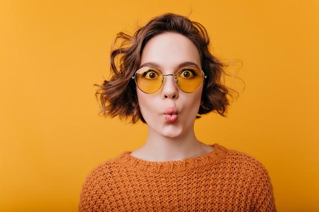 Close-upportret van mooi meisje dat op gele ruimte met kussende gezichtsuitdrukking wordt geïsoleerd