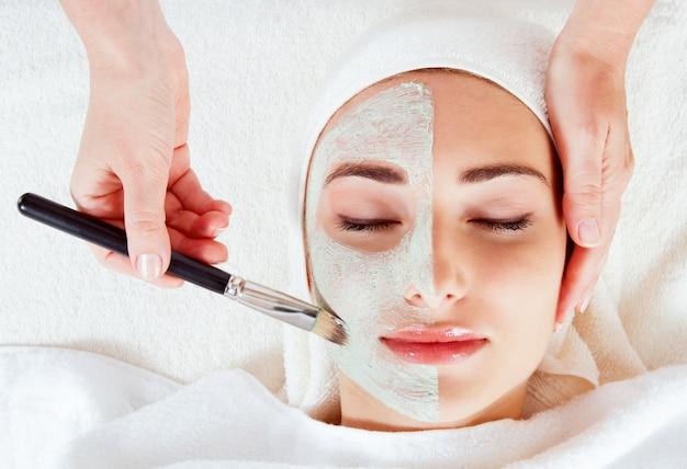 Close-upportret van mooi meisje met een handdoek op haar hoofd die gezichtsmasker toepassen