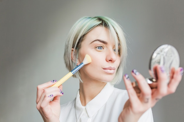 Close-upportret van mooi meisje met kort wit haar op grijze achtergrond. ze draagt een witte jurk, kijkt naar de spiegel in de hand en poedert haar gezicht.