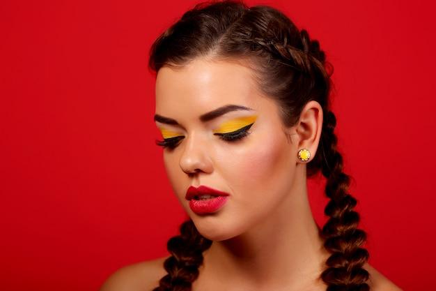 Close-upportret van mooi modelgezicht met neon heldere gele maniersamenstelling en met grote kristalring