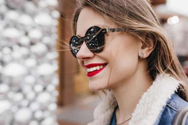 Close-upportret van mooi vrouwelijk model met rode lippen die op straat stellen. buiten foto van vrolijk wit meisje goede emoties uitdrukken.