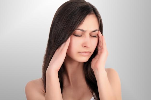 Close-upportret van mooi ziek meisje die aan hoofdpijn lijden