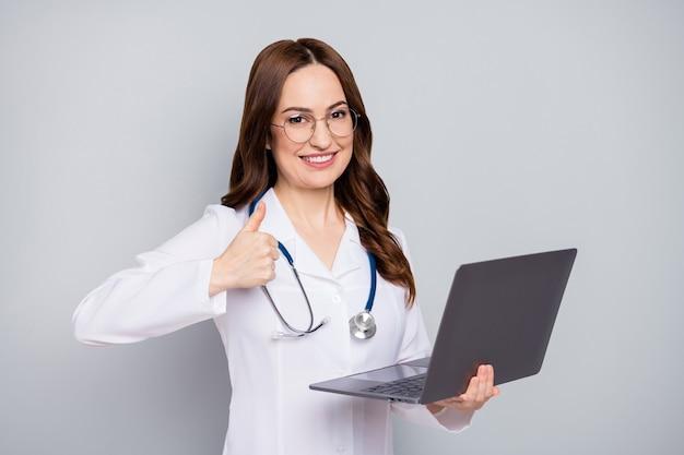 Close-upportret van mooie aantrekkelijke blije vrolijke golvendharige doc phonendoscope stethoscoop in handen houden laptop weergegeven: thumbup geïsoleerd over grijze pastelkleur achtergrond