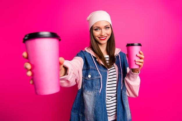 Close-upportret van mooie aantrekkelijke mooie innemende vrolijke vrolijke meid die koffiekopjes in de hand houdt die u nieuwe smaak geven geïsoleerd op heldere, levendige glans levendige roze fuchsia kleur