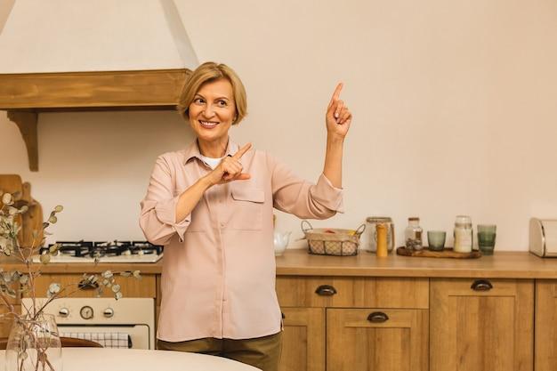 Close-upportret van mooie bejaarde rijpe oude hogere vrouw in de keuken na het koken. wijzende vinger naar kopieerruimte, plaats voor tekst.