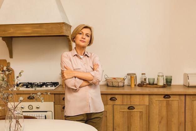 Close-upportret van mooie bejaarde rijpe oude hogere vrouw in de keuken na het koken.