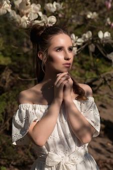 Close-upportret van mooie donkerbruine vrouw die zich in bloeiende magnoliatuin bevindt