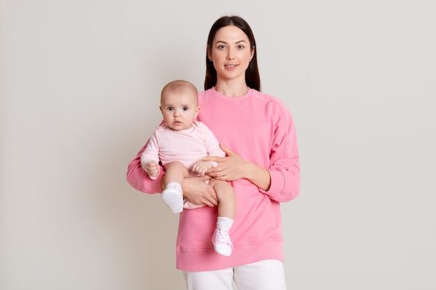 Close-upportret van mooie donkerharige vrouw die roze sweatshirt en broek draagt die haar dochtertje op witte muur bij handen houdt. familie, liefde, levensstijl, moederschap en tedere momenten.