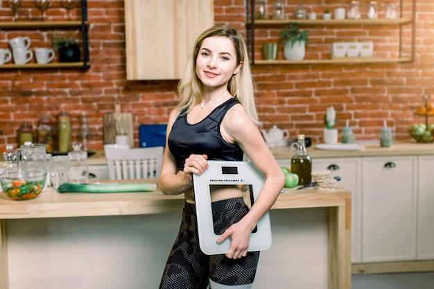 Close-upportret van mooie geschikte vrouw die zich in haar keuken met een gewichtsschaal in haar hand op de achtergrond van de keukentafel van de bakstenen muurmier bevinden. afvallen, dieet en gezonde voeding