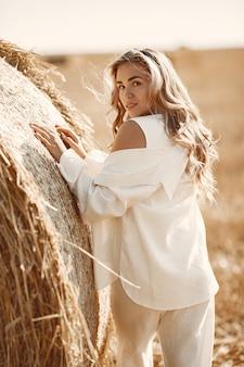 Close-upportret van mooie glimlachende vrouw. de blonde op een baal hooi. een tarweveld op de achtergrond.