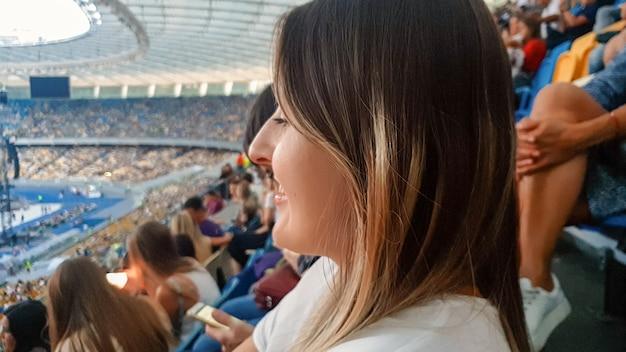 Close-upportret van mooie glimlachende vrouw met lang haar die op de stadiontribunes zit en op het sportrsgebeurtenis of de voetbalwedstrijd wacht